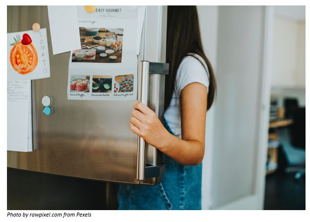 A girl looking at the fridge.
