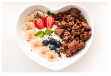 A heart shaped plate with fruits and oats with milk or joghurt.