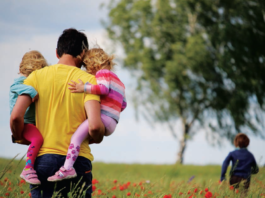 A man holding two kids in a field