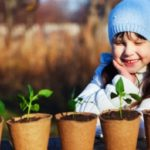 A girl looking at plants in environmental friendly pots.
